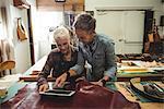 Craftswomen using digital tablet in workshop