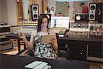 Audio engineer using digital tablet in music studio