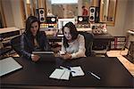 Audio engineers using digital tablet and mobile phone in recording studio