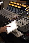 Audio engineer using digital tablet in recording studio