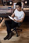 Audio engineer using digital tablet near sound mixer in recording studio