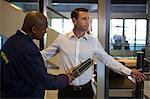 Security guard frisking a passenger at airport terminal