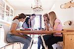 Mature woman assisting teenage girls in doing homework at home