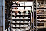 Baker arranging cardamom rolls on tray at bakery