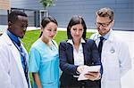 Team of doctors discussing over digital tablet in hospital premises