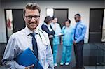 Portrait of smiling doctor holding medical report in hospital corridor