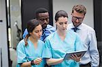 Medical team discussing over digital tablet in hospital corridor
