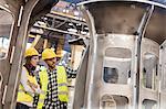 Steel workers examining part in factory