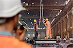 Steel workers adjusting crane hooks in factory