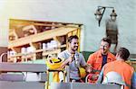 Smiling steel workers enjoying coffee break ins factory