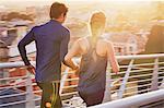 Runner couple running on sunny urban footbridge at sunrise