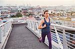 Female runner running on urban footbridge