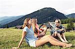 Three female adult friends eating apple in field, Sattelbergalm, Tirol, Austria