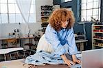 Dressmaker in workshop using laptop