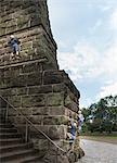 Boys climbing stone wall