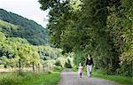 Mother and daughter walking on rural road, Porta Westfalica, North Rhine Westphalia, Germany