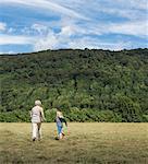 Rear view of grandmother with grandson jogging across field, Porta Westfalica, North Rhine Westphalia, Germany