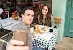 Couple at pavement cafée talking selfie