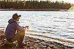 Mid adult man sitting beside lake, looking at view, Flagstaff, Arizona, USA