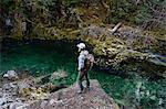 Man standing on rock looking away at river, Opal Creek, Oregon, USA