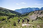 Hikers walking across valley, Enchantments, Alpine Lakes Wilderness, Washington, USA