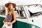 Woman leaning against vintage camper van looking away