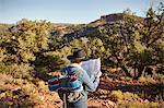 Woman in rural setting, looking at map, rear view, Sedona, Arizona, USA