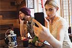 Woman taking selfie while man talking on phone