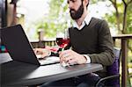 Man using laptop while having glass of wine