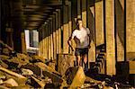 Man running under bridge, Wapping, London, UK