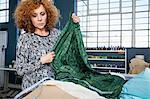 Mature female fashion designer measuring textiles on workshop table