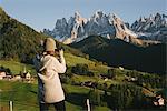 Woman taking photograph, Santa Maddalena, Dolomite Alps, Val di Funes (Funes Valley), South Tyrol, Italy
