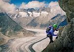 Female climber climbing rock face over Aletsch Glacier, Canton Wallis, Switzerland