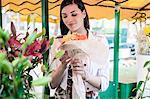 Female tourist with bunch of flowers at market stall, Split, Dalmatia, Croatia