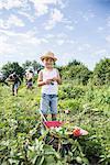 Small boy holding switchblade with wheelbarrow in community garden, Bavaria, Germany