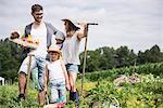 Family harvesting vegetables in community garden, Bavaria, Germany