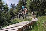 Two mountain bikers riding on footbridge through forest, Zillertal, Tyrol, Austria