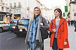 Two female friends walking in street