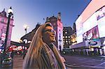 Young woman exploring city at dusk
