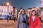 Two female friends crossing road, dusk