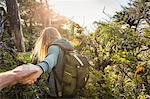 Female hiker leading boyfriend through forest, Pacific Rim National Park, Vancouver Island, British Columbia, Canada