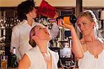 two girls plus barkeeper, having fun