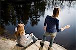 Two women throwing stones in lake