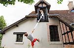 Man climbing sheet to girlfriend's room