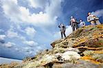 Businessmen standing on cliff edge