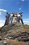 Businessmen cheering on cliff