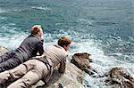 Businessmen peering over cliff edge