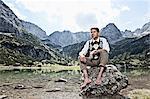 Man in bare feet sitting by lake