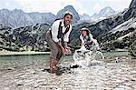 Couple splashing in lake