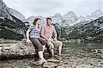 Smiling couple dangling feet in lake